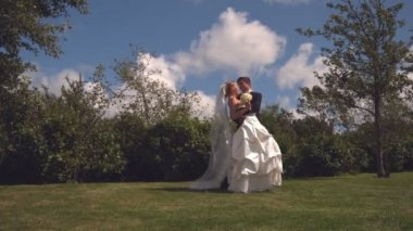 Beautiful newlywed couple embracing and kissing — Stock Video
