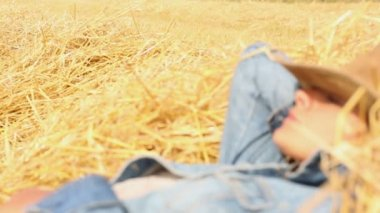 Peaceful woman with cowboy hat lying in hay — Stock Video