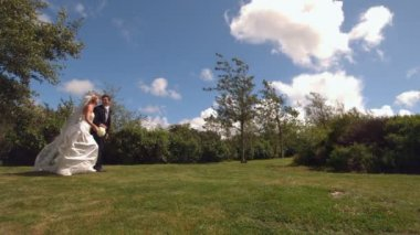 Happy newlywed couple running in a park in slow motion