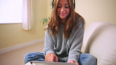 Cheerful attractive brunette sitting on couch listening to music — Stock Video