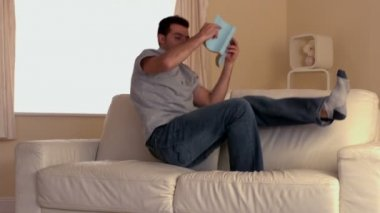 Attractive man jumping on couch with book — Stock Video