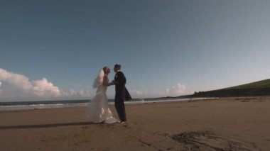 Attractive newlywed couple running on the beach — Stockvideo
