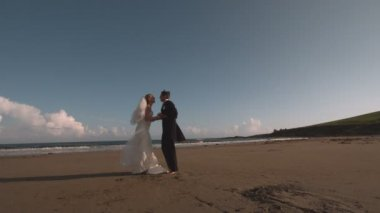 Attractive newlywed couple running on the beach — Stock Video