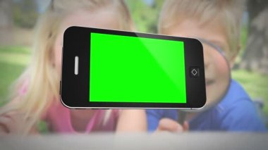 Smartphone with green screen in front of family outdoors — Stock Video