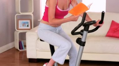 Sporty woman exercising on exercise bike at home — Stock Video