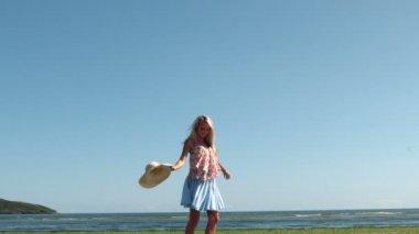 Nádherná blondýnka drží slamák předení na pláži — Stock video