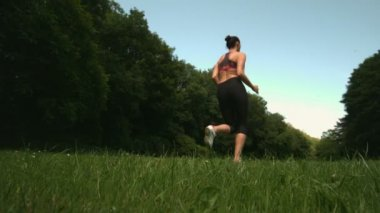 Low angle view of sporty womans back running on grass — Stock Video