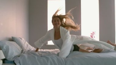 Cheerful blonde jumping on bed — Stock Video