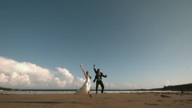 Happy newlywed couple jumping in the air on the beach — Стоковое видео