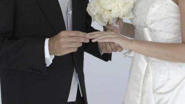Happy newlywed groom sliding wedding ring on brides finger — 图库视频影像