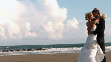 Beautiful newlywed couple hugging on the beach — Stockvideo