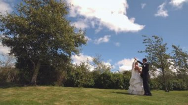 Happy newlywed couple dancing in a park — Stockvideo