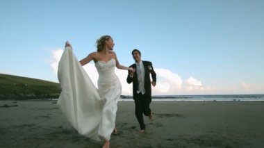 Happy newlywed couple running on the beach — Stock video