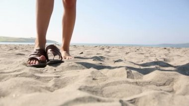 Woman putting on sandals on the beach — Stock Video #33431527