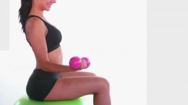 Side view of fit woman sitting on exercise ball training with dumbbells — Stock Video