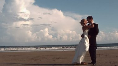 Happy newlywed couple kissing on the beach — 图库视频影像