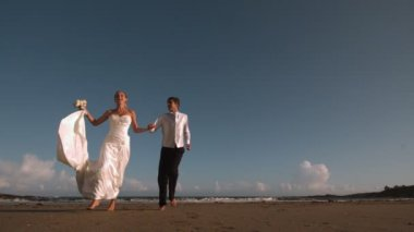 Cheerful bridal couple running on the beach — Stock Video