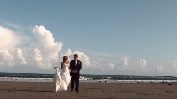 Heureux mariés marchant sur la plage — Vidéo