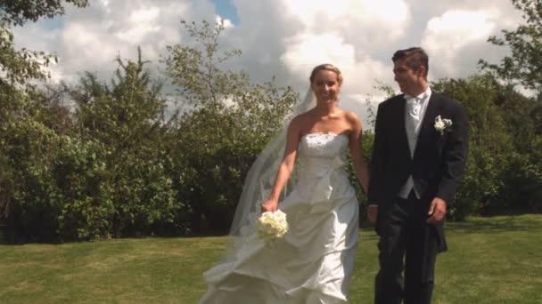 Couple de jeunes mariés à pied et baiser — Vidéo