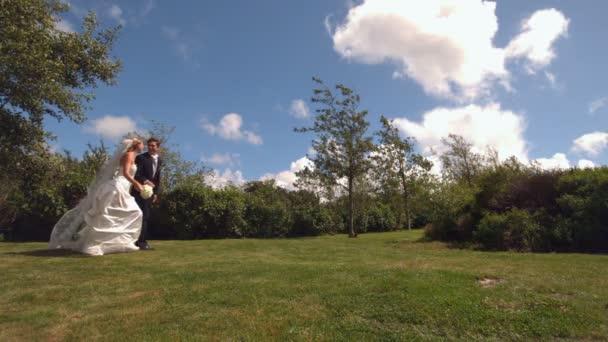 Coppia di sposini felici in esecuzione in un parco — Vidéo