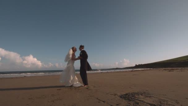 Mariés attrayant en cours d'exécution sur la plage — Vidéo