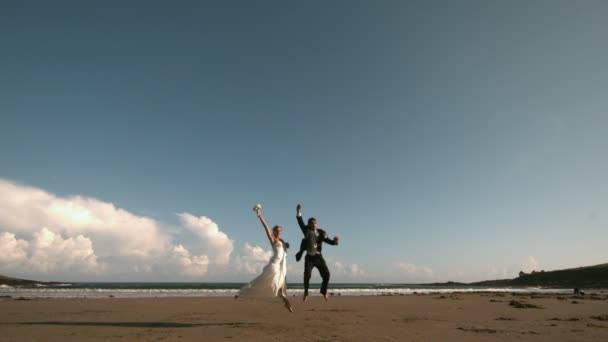 Couple de jeunes mariés heureux sautant en l'air sur la plage — Vidéo