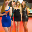 Smiling woman standing in front of her friends holding cocktail — Stock Photo #33440031