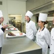 Stock Photo: Three chefs presenting their dessert plates to head chef