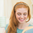 Foto Stock: Happy redhead reading a book on the couch and holding mug