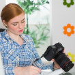 Focused photographer sitting at her desk holding her camera — Stock Photo