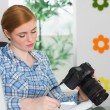 Stock Photo: Focused photographer sitting at her desk holding her camera