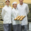 Stock Photo: Young female baker presenting some rolls