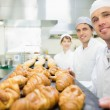 Three young bakers posing in a bakery — Foto de Stock