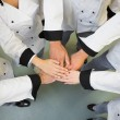 Five chefs joining hands in a circle — Stock Photo