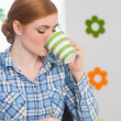 Stock Photo: Redhead writing on notepad at her desk and drinking coffee