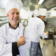 Experienced male chef posing in a kitchen — Stock Photo