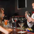 Handsome bartender serving cocktail to beautiful woman — Stock Photo