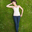 Pretty woman lying on a lawn — Stock Photo