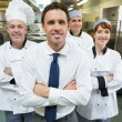 Restaurant manager posing in front of team of chefs — Stock Photo