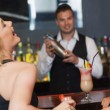 Handsome bartender working while gorgeous friends laughing — Stock Photo