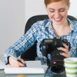 Smiling photographer sitting at her desk looking at camera — Foto Stock