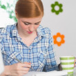 Focused redhead writing on notepad at her desk and holding coffee — Stock Photo