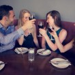 Smiling friends clinking wine glasses — Stock Photo