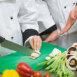 Chef gesturing at his colleagues sliced mushrooms — Stock Photo
