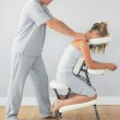 Masseur treating shoulders of client in massage chair — Stock Photo