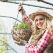 Pretty blonde showing a hanging flower basket — Stock Photo