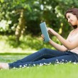 Happy woman leaning against a tree working with her tablet — Stock Photo