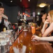 Handsome bartender making cocktails for beautiful women — Stock Photo