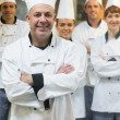 Five chefs wearing uniforms while posing in a kitchen — Stock Photo