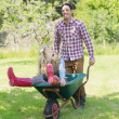 Man pushing his girlfriend in a wheelbarrow — Stok fotoğraf